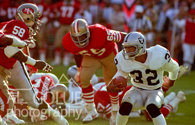 San Francisco 49ers vs. Los Angles Raiders at Candlestick Park Saturday, August 4, 1984..Pre-season Game. .Los Angles Raiders Running Back Marcus Allen (32) faces San Francisco 49ers Linebacker Keena Turner (58) and Defensive End Lawrence Pillers (65)..