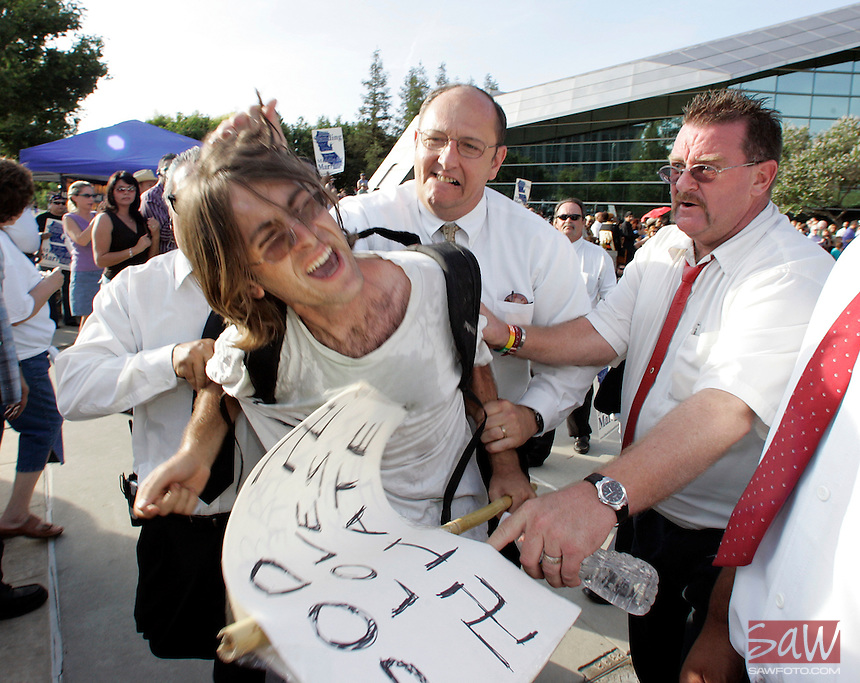 "FRESNO,CA - May 31,2009: Fresno resident Sean Zweifler,21, is accosted by members of the Cornerstone Church security during a Sunday rally billed as a "" Celebration of Marriage "" at Fresno City hall on Sunday, May 31, 2009. Zweifler, who says his mother is lesbian, marched through the center of the rally  chanting "" God loves Hate"" before being pushed back across the street."
