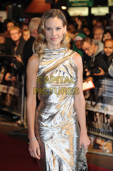 "HILARY SWANK.The 54th BFI London Film Festival screening of ""Conviction"" at Vue cinema, Leicester Square, London, England, UK, October 15th 2010 .LFF half length sleeveless silver shiny metallic wavy hair dress gold clutch bag  .CAP/WIZ.© Wizard/Capital Pictures."