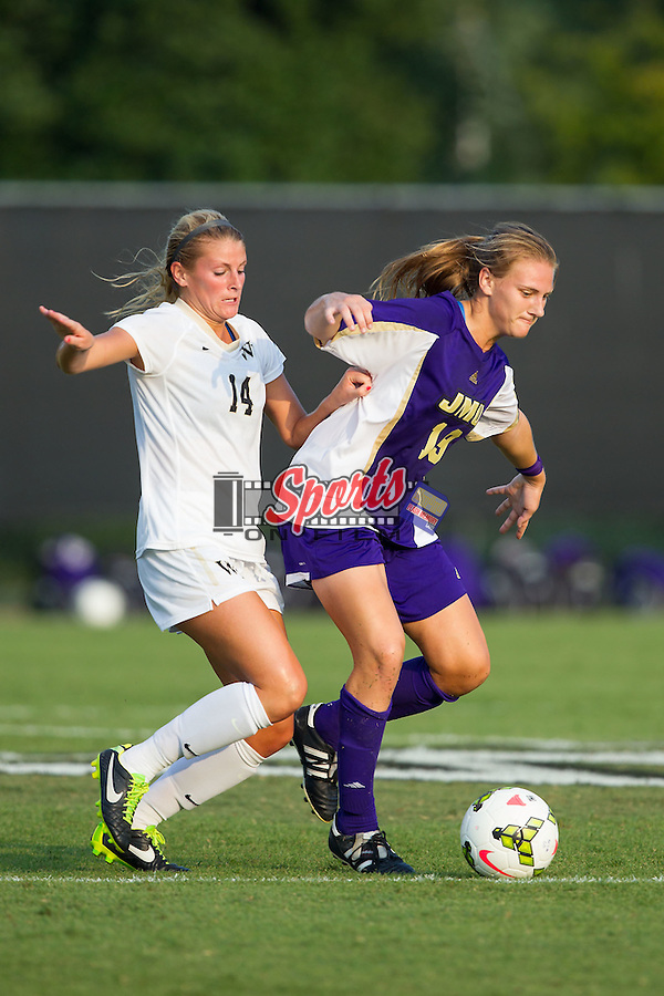 Ashley Herndon (19) of the James Madison Dukes keeps the ball away from Taylor Waters (14) during second half action at Spry Soccer Stadium on August 29, 2014 in Winston-Salem, North Carolina.  The Dukes defeated the Demon Deacons 2-1.   (Brian Westerholt/Sports On Film)