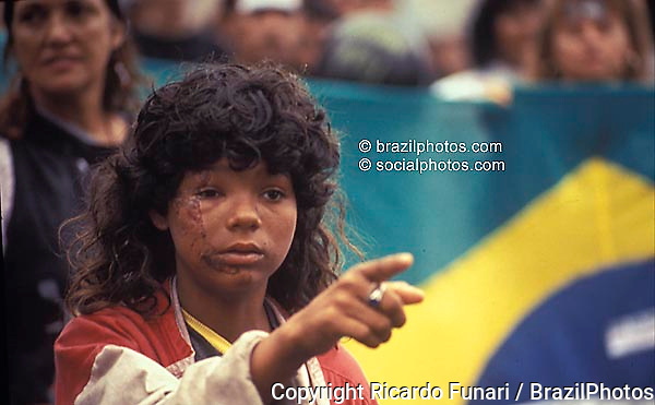 Rio de Janeiro, Brazil..Street girl with hurt face in a political demosntration. Violence against children. Brazil flag in background.