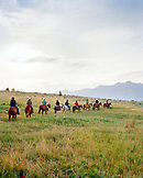 USA, Montana,  cowboys and cowgirls riding horses in an open landscape