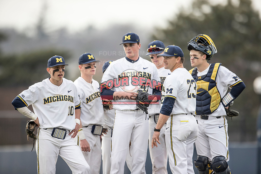 Michigan Wolverines head coach Erik Bakich (23) and players Blake Nelson (10), Jack Blomgren (18), Jesse Franklin (7) and Blake Keener (39) surround pitcher Tommy Henry (47) on the mound against the Maryland Terrapins on April 13, 2018 in a Big Ten NCAA baseball game at Ray Fisher Stadium in Ann Arbor, Michigan. Michigan defeated Maryland 10-4. (Andrew Woolley/Four Seam Images)