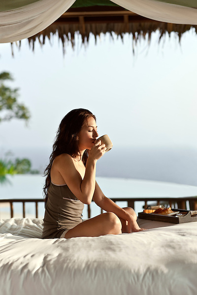 A woman enjoys breakfast in bed and an ocean view in the Masters Bedroom of the Hilltop Reserve, a three-bedroom private pool villa at Six Senses Hideaway Yao Noi. Thailand.