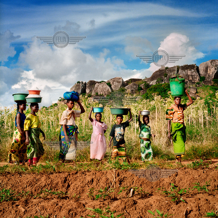 Women and children return from working in the fields.