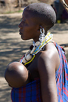 A Masai mother and her baby in a village near the Serengeti National Park, Tanzania. She has the tradtional shaved head and she is wearing the traditional ornate beaded earrings and necklace.