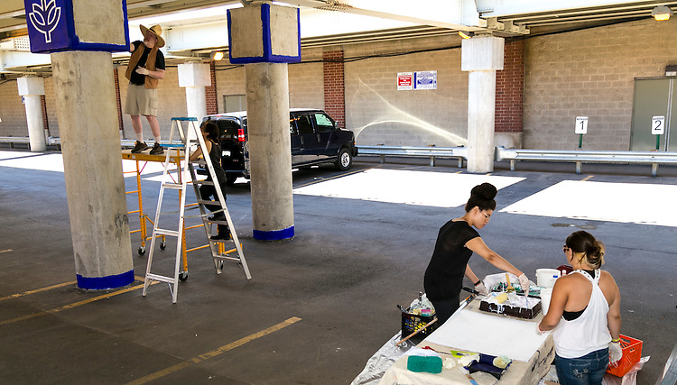 """Brother Mark Elder, C.M., with the aid of former DePaul students Emanuel Cajijas, Christina Morris, and Joanna Geordano,hangs a series of murals, Saturday, Aug. 6, 2016, on the massive concretepillars supporting the CTA's """"L"""" station and tracks at Fullerton. Throughout the spring 2016 quarter and into the summer, Brother Mark and his Mural Class students created several portraits and historically-themed murals that will eventually wrap the support columns, which runs right through DePaul's Lincoln Park Campus. The murals depict many prominent, historical figures that have made an impact on DePaul University. (DePaul University/Joel Dik)"""