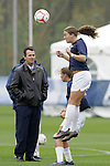 05 November 2008: North Carolina's Courtney Jones (right) heads the ball in pregame warmup as head coach Anson Dorrance (left) looks on. The University of North Carolina defeated the University of Miami 1-0 at Koka Booth Stadium at WakeMed Soccer Park in Cary, NC in a women's ACC tournament quarterfinal game.