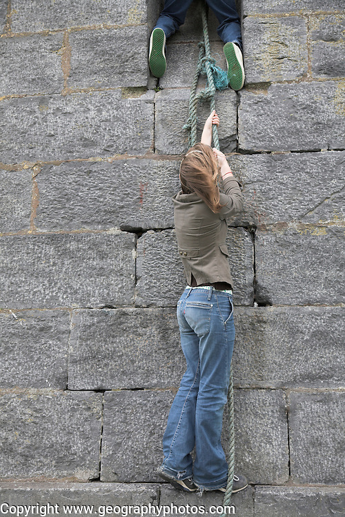 Model released brother and sister twins pulling themselves up a rope against a stone wall