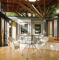 The open-plan dining area has a Norman Foster 'Moma' table and 'Lord Yo' dining chairs by Philippe Starck