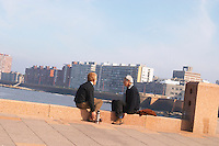 Two men sitting on a red stone bench. Men facing each other talking conversing and drinking mate herbal tea from a thermos hot water flask. Modern city buildings in the background., on the riverside seaside walk along the river Rio de la Plata Ramblas Sur, Gran Bretagna and Republica Argentina Montevideo, Uruguay, South America