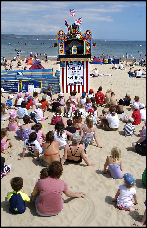 BNPS.co.uk (01202 558833)Pic: PhilYeomans/BNPS<br /> <br /> Mark Poulton performing his Punch and Judy show on Weymouth beach.<br /> <br /> One of Britain's longest-running Punch and Judy shows is in jeopardy because the man behind it says he cannot afford to keep it going.<br /> <br /> Mark Poulton, who runs the show in Weymouth, Dorset, said a shorter holiday season has hit his takings but his expenses and overheads remain the same.<br /> <br /> He blamed strict rules preventing parents from taking their children out of school during term-time, reducing his usual 17-week season to just seven weeks, and said school groups have also stopped coming in July due to budget cuts.<br /> <br /> The seaside town has had a Punch and Judy show since 1880, but Mr Poulton says he relies on donations and with audiences dwindling he will not be able to continue the seaside tradition past this summer season without outside support.