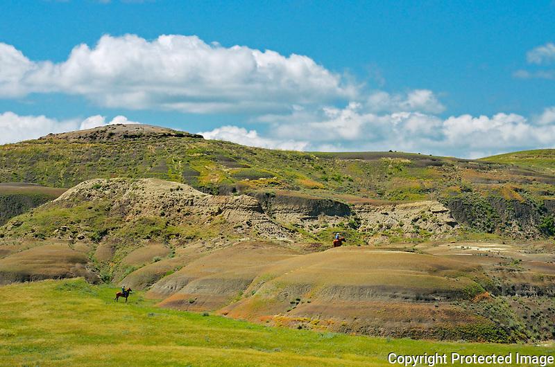 Riding horses in the Killdeer Badlands (East Block)<br />Grasslands National Park<br />Saskatchewan<br />Canada