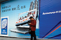 A man holds two mobile phones in front of an advert for Lenovo computers in Guangzhou, China.  Lenovo, formally Legend, is China's largest computer manufacture and one of the export success stories from China.                                                                                                                .