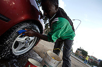 Zelalem, 17 years old, washes the BMW of a rich ethiopian earning for his services 120 ETB ( 14 USD ) per month, in Addis Ababa, Ethiopia on Wednesday May 23 07..Zelalem lived with other 5 friends in shelters made from unused sewage pipes just off Bole road, the main drag in Addis Ababa. They were all kicked out  when bulldozers flattened the area to build a performance and commercial center for the upcoming ethiopian millennium.