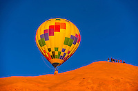 Hot air balloon flying in front of people on top of huge monolithic rock during the Red Rock Balloon Rally, Red Rock State Park, near Gallup, New Mexico USA.