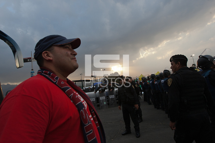 USA fan Doug Morales takes in Mexican police officers in riot gear forming a perimeter around a bus of USA fans arriving for the USA vs. Mexico World Cup Qualifier at Azteca stadium in Mexico City, Mexico on March 26, 2013.