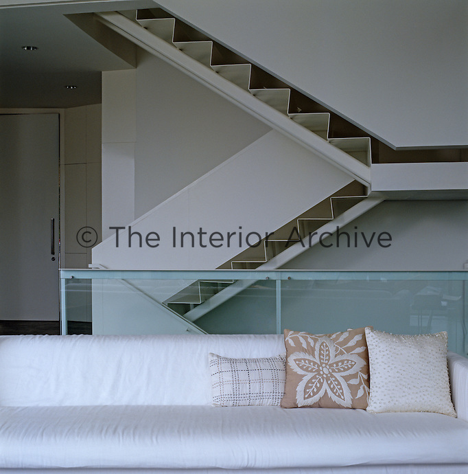 A glass balustrade and side view of the staircase seen from the living room