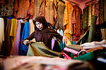 A woman cuts fabric at the market, in Banda Aceh, Indonesia, on Thursday, Nov. 19, 2009