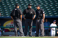 Umpires Luis Hernandez, Kyle Wallace and Jose Matamoros (from left) talk at home plate during a Texas League game between the Northwest Arkansas Naturals and the Arkansas Travelers on May 30, 2019 at Arvest Ballpark in Springdale, Arkansas. (Jason Ivester/Four Seam Images)