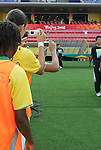 12 August 2008: Brazil substitutes take personal photos of the entrance of the Brazilian flag.  The women's Olympic team of Brazil defeated the women's Olympic soccer team of Nigeria 3-1 at Beijing Workers' Stadium in Beijing, China in a Group F round-robin match in the Women's Olympic Football competition.