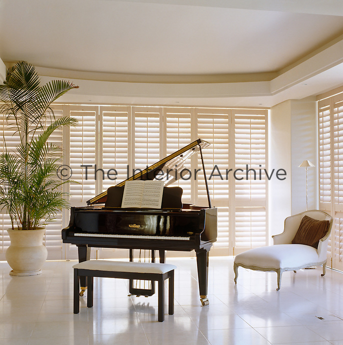 A grand piano at one end of the living room stands against a wall of white louvred shutters on a white tiled floor