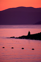 Man sitting on rocks contemplating sunset, by the ocean at English Bay in the West End,  Vancouver, BC