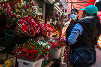 NEW YORK, NY - MAY 10: A man wearing a face mask offers a bouquet of flowers to a woman in Jackson Heights on Mother's Day on May 10, 2020 in Queens, New York. COVID-19 has spread to most countries in the world, claiming more than 283,000 lives and more than 4.1 million people infected, Queens has been one of the places most affected by the Coronavirus. (Photo by Pablo Monsalve / VIEWpress via Getty Images)