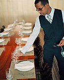 USA, California, Los Angeles, waiter arranging dinner table with wine glass at Craft Restaurant.