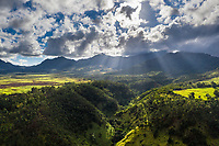 Aerial view of sunrays beaming over Wahiawa fields, with Mount Ka'ala and Wai'anae Range, O'ahu.