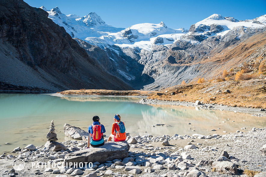 Two trailrunners sitting next to an alpine lake, the Lej da Vadret, in the Rosegtal while on a running tour from Pontresina, Switzerland