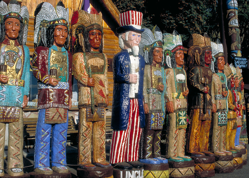 A row of colorful wooden Indian or cigar Indian sculptures are displayed along the curb of a popular shopping area in Idaho. Included is an Uncle Sam sculpture. Boise Idaho.