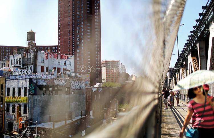 A pedestrian shields herself from the afternoon sun walking across the Manhattan bridge toward Brooklyn, with the graffitied buildings of Chinatown in the background, in New York, New York, on July 16, 2015.
