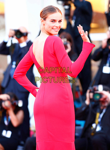 Kasia Smutniak.The Opening Ceremony of the 69th Venice International Film Festival at Palazzo del Cinema, Venice, Italy. .August 29th, 2012 .half length red dress hand on hip hand arm waving looking over shoulder .CAP/IPP/GR.©Gianluca Rona/IPP/Capital Pictures.