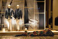 Milano feb.2013.Un senza fissa dimora dorme avvolto in una coperta vicino alla vetrina di un negozio in San Babila, nel pieno centro di Milano. Numerosi sono i senza casa che trovano riparo la notte nelle vie del centro. Di giorno vagano alla ricerca di cibo e di posti riparati per resistere ai rigori dell'inverno..A homeless sleeps wrapped in a blanket next to a shop in San Babila, in the heart of Milan. Many homeless find shelter at night in the streets of downtown. By day wander in search of food and places repaired to withstand the rigors of winter..Foto Livio Senigalliesi