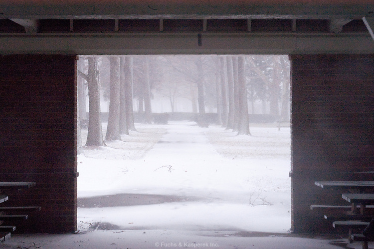 Blowing snow and a winter scene is framed by the entrance to a picnic pavillion at the Huntington Reservation of the Cleveland MetroParks.