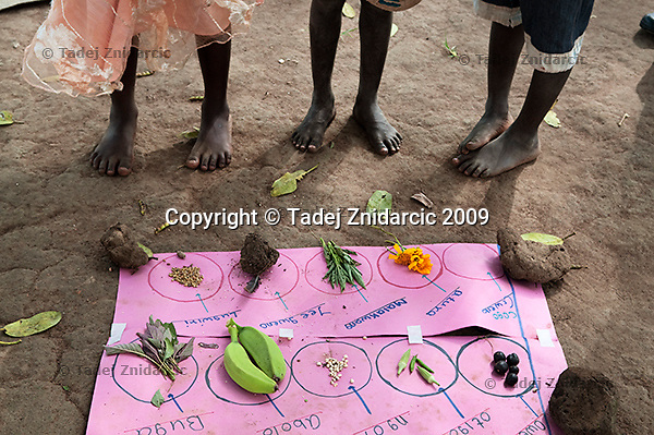 Children stand next to a learning aide that names fruits and vegetables in Acholi language that is spoken in northern Uganda.