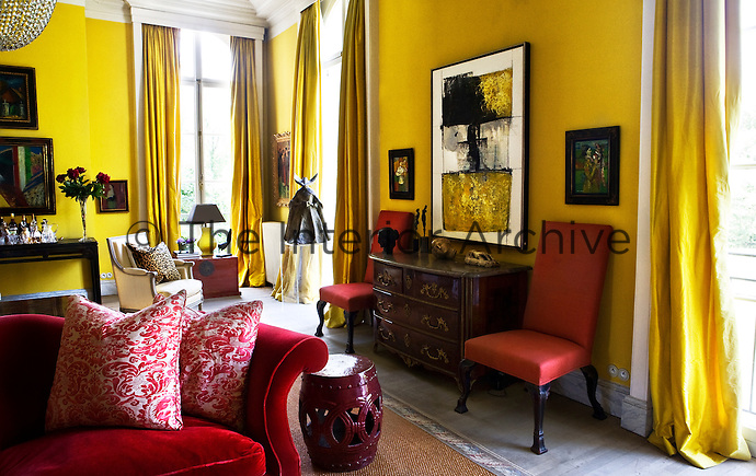 The Bright Golden Yellow Walls And Matching Curtains Of Living Room Are In Bold Contrast