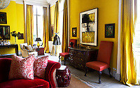 The bright golden yellow walls and matching curtains of the living room are in bold contrast to the red soft furnishings