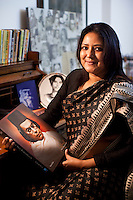 Anindita Kazi sits for a portrait at her reading desk surrounded by photos and books of her grandfather Kazi Nazrul Islam and Rabindranath Tagore as she holds her mother's recently released book on Nazrul Islam, in Calcutta, West Bengal, India, on 17th January, 2012. The West Bengal government's attempts to rename one of its historic buildings after a Bengali poet has met with controversy. Kazi Nazrul Islam, Bangladesh's national poet's legacy has always been debated, including his relationship with other Indian intellectuals such as Rabindranath Tagore, who won the Nobel Prize for Literature in 1913. In an attempt to quell doubts, Anindita Kazi, Mr Islam's grand daughter will release a CD in which she reads from unpublished letters between the two poets to show their regard for each other. Photo by Suzanne Lee for The National (online byline: Photo by Szu for The National)