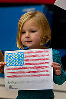 A young girl holds a paper flag she created for observance of Veterans Day at Cherrington Elementary in Westerville, Ohio. The students gathered in the auditorium to listen to two U.S.Army soldiers talks about their experiences and presented gifts to the two men.