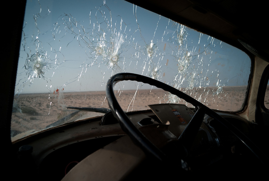 Multiple bullet holes and bloody finger prints on truck windshield on the road to Bin