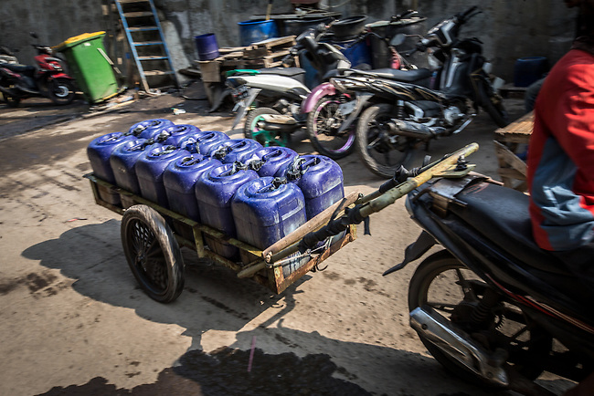 13 August 2019, Jakarta, Indonesia: A local man loads up water barrels for delivery on the streets of Muara Baru, North Jakarta below the sea wall. Local residents were speaking about the lack of water facilities that the local poor population has access to. Water is hauled in each day by motorcycle and trucks and by hand to allow residents of the kampungs to  buy it for washing and to do laundry. Separate water is needed for drinking. The Jakarta Governor is proposing a program to send in trucks of water for the locals to get for free. They are living in villages below the seawater line on the coast of Jakarta that is sinking faster than anywhere else in the world so they have the position of being surrounded by water yet not having access to clean supplies. Picture by Graham Crouch/The Australian