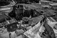 SALVADOR, BRAZIL - FEBRUARY 13, 2014: A woman stands on the roof of a home in a favela overlooking the Bonocô neighborhood as the abandoned metro system stretches off into the distance on February 13, 2014 in Salvador, Brazil. The metro system began construction over 13 years ago and has never operated. A new concessionary signed a contract for the maintenance and management of the metro last year and promises to have at least part of it functioning in 2014.<br /> <br /> Daniel Berehulak for The New York Times