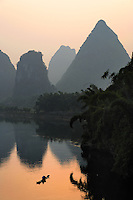 A man paddles a bamboo raft on the Lijiang River under the rising sun and karst mountains, Yangshuo, Guanxi, China