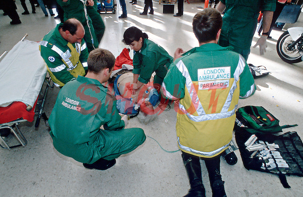 Paramedic ambulance crews attend a cardiac arrest victim on a train station platform. A paramedic is performing CPR on the victim. This image may only be used to portray the subject in a positive manner..©shoutpictures.com..john@shoutpictures.com