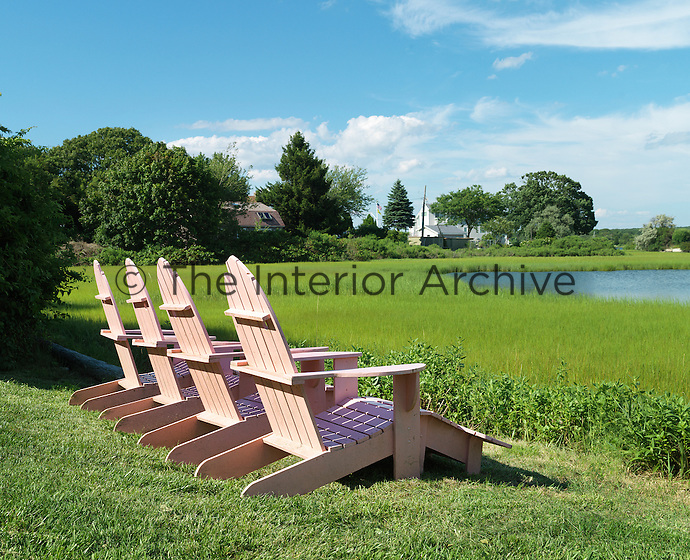 A row of pink Adirondack chairs have been positioned in the garden overlooking the Great Salt Pond