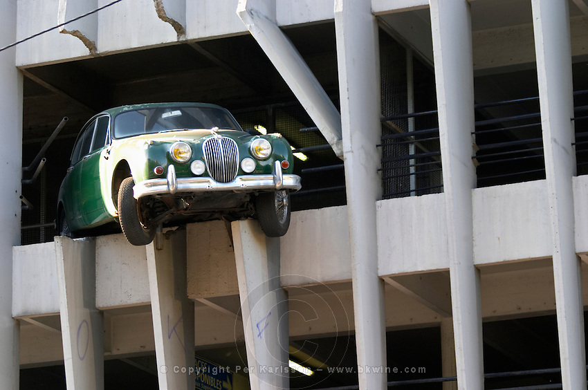 Parking garage with an old Jaguar falling out, original sculpture. Bordeaux city, Aquitaine, Gironde, France