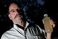 Craig Sautner of Dimock, PA, holds a bottle of his contaminated tap water collected in March 2010. Their water problems started in September 2008 after natural gas drilling on their property a month earlier. &quot;Our water smells of diesel fuel,&quot; says Sautner. &quot;In our water, we've found aluminum, manganese, chloride, iron, magnesium, sodium, strontium-T, all above the EPA limits, and TDS [Total Dissolved Solids] and other elements we can't disclose yet.&quot; <br /> <br /> Craig and Julie Sautner are among 14 families along Carter Road whose drinking water wells became contaminated with methane and other chemicals. Cabot Oil and Gas, the company held responsible by the Pennsylvania Department of Environmental Protection, has had at least 21 spills in Dimock Township in less than two years. The Sautners' well has so much methane that Craig can sometimes light his water on fire, and Cabot had to install an exhaust pipe to vent off excess methane.<br /> <br /> Hydraulic fracturing or &quot;fracking&quot; is new method of drilling for natural gas: millions of gallons of water, sand and proprietary chemicals are pumped down a well under high pressure. The pressure fractures the shale, opening fissures so that natural gas can flow more freely. In August 2010, fracking is being widely used in the Marcellus Shale formation under Pennsylvania while New York considers a moratorium until the environmental effects can be reviewed. <br /> <br /> The 2005 Energy Policy Act exempted natural gas drilling from the Safe Drinking Water Act. Scientists have identified volatile organic compounds (VOCs) such as benzene, ethylbenzene, toluene, methane and xylene that have been found in contaminated drinking water near drilling sites.<br /> <br /> &copy; Michael Forster Rothbart<br /> www.mfrphoto.com <br /> 607-267-4893 o 607-432-5984<br /> 5 Draper St, Oneonta, NY 13820<br /> 86 Three Mile Pond Rd, Vassalboro, ME 04989<br /> info@mfrphoto.com<br /> Photo by: Michael Forster Rothbart<br /> Date: 8/2010    File#:  Canon 5D digital camera frame 68410