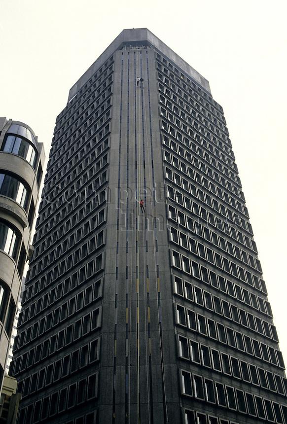 Three men abseiling a high rise building